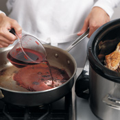 Deglaze the sauté pan with red wine, scraping up any browned bits left on the bottom.