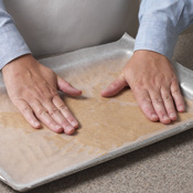 For a smooth, even layer, press dough with waxed paper.