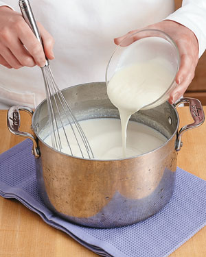 Adding yogurt starter to cooled milk for homemade yogurt