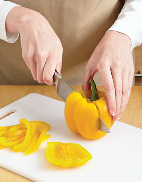 To cut a bell pepper for easy slicing, stand it on its end and cut off the four lobes around the stem.