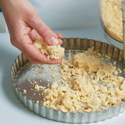 Scatter the crumbly dough in the tart pan, making sure to spread it into the corners.