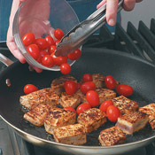 Add tomatoes to the seared tuna and sauté just until the skins begin to blister.