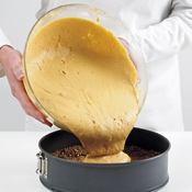 Pour the filling into the cooled prebaked crust. Shake the pan to level the cheesecake filling.