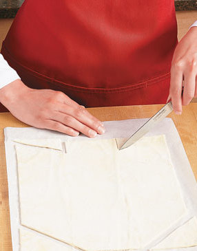 Roll pastry, transfer to parchment, then cut off top corners. Notch bottom to create end flaps.