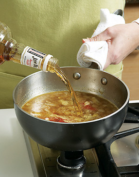 Add bourbon to the sauce off heat. High-proof alcohol will ignite if exposed to a flame.