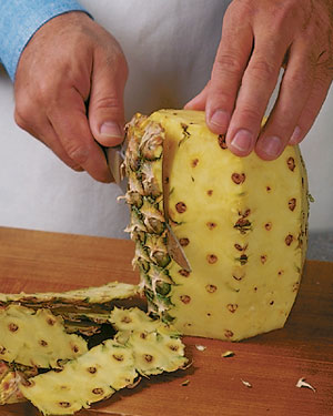 "Pineapple is one of the more difficult fruits to cut, because it's large, has a spiky skin and those prickly ""eyes"" inside the fruit once you've cut it. Here's a way to peel pineapple with as little waste as possible and get the bonus of decorative slices"