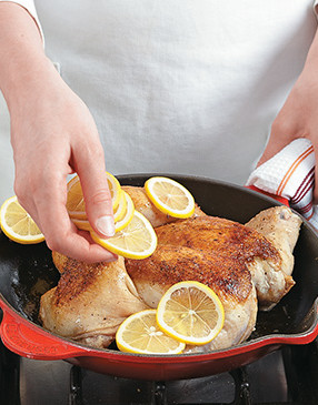 Top the seared chicken with lemons, then roast in the oven. The lemons add flavor to the chicken as they caramelize.