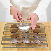 To decorate baked cookies, scoop some powdered sugar into a fine-meshed sieve and tap repeatedly.