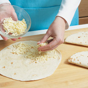 To prepare the quesadillas, sprinkle 1/2 cup cheese on half of each tortilla, then fold over and grill until toasted.