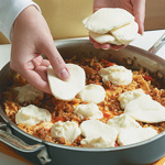 For the finishing touch before broiling, top the lasagna with ricotta and fresh mozzarella.