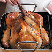 Baste turkey with drippings from the bottom of the pan to keep the skin moist and help it brown.