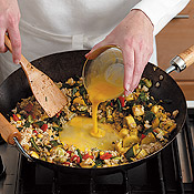 Form a well in the center of stir-fry to scramble eggs. This keeps them contained so they´ll cook faster.