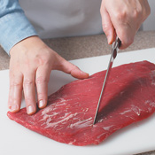 Using just the tip of a knife, make shallow cuts in a diamond pattern across the grain of the meat.