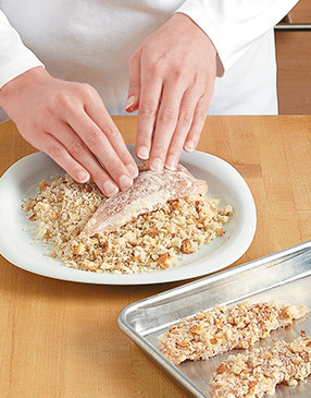 Firmly press both sides of the chicken into the almond and bread crumb mixture so the crumbs stick.