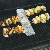 To prevent the ends of the skewers from burning, arrange the exposed end of the skewers over a piece of foil.