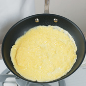 Tilt skillet to roll excess egg mixture around to the edges of the omelet.
