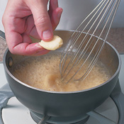 Whisk <em>beurre manié</em> and thyme into simmering sauce. Heat and stir until sauce is slightly thickened.