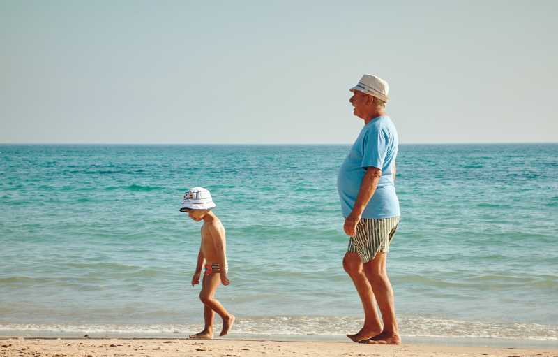 Grandparent with grandchild on beach