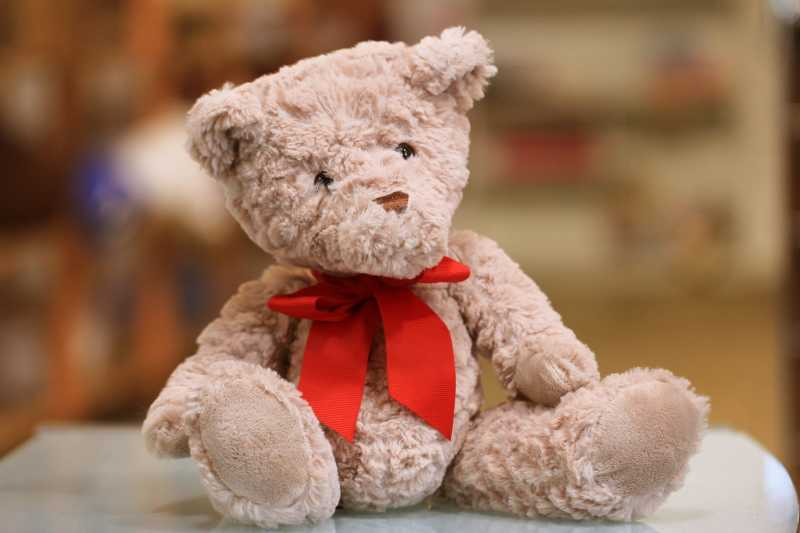 This is an image of a brown teddy bear with a red bow.