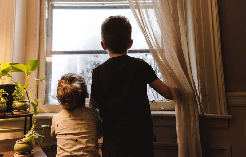 Photo of children looking out the window