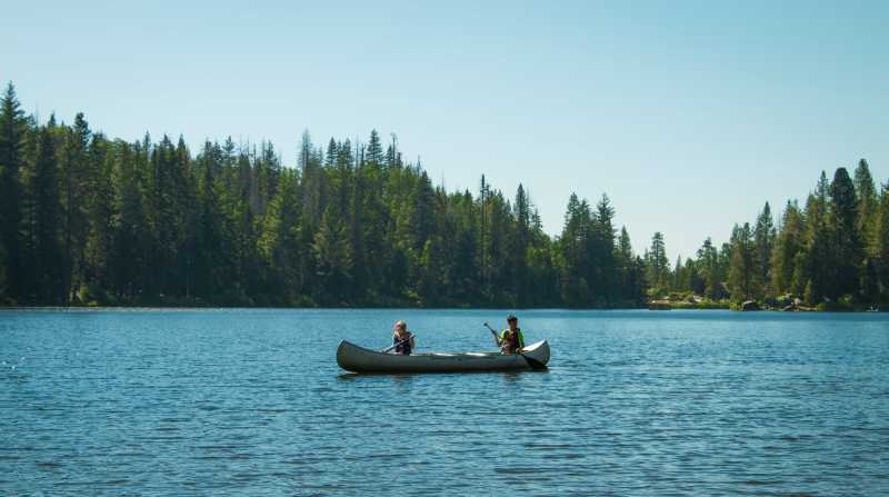 Kids canoe on lake