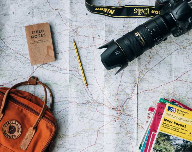 This is a photo of a map, guide books, camera and backpack.