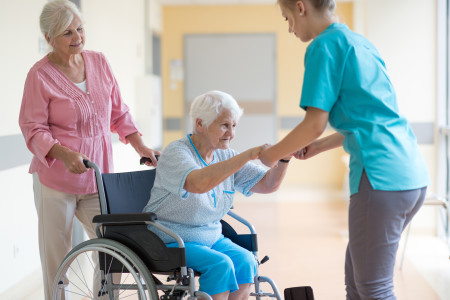 nurse-helping-woman-in-wheelchair