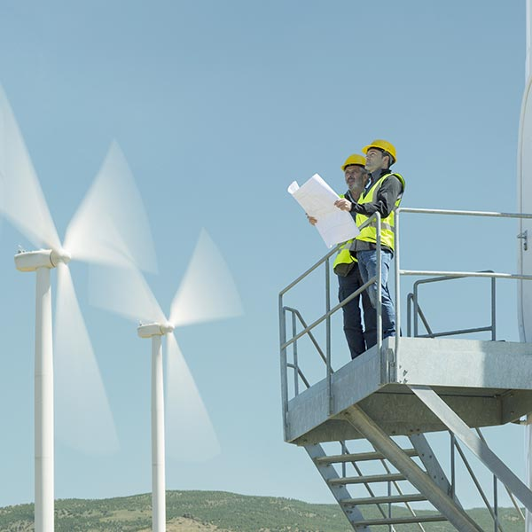 Workers standing on a metal platform with windmills in the background