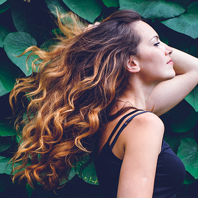 Show Us How you go Waterl<ss on Instagram - girl poses against foliage, she has long wavy, ombre hair.