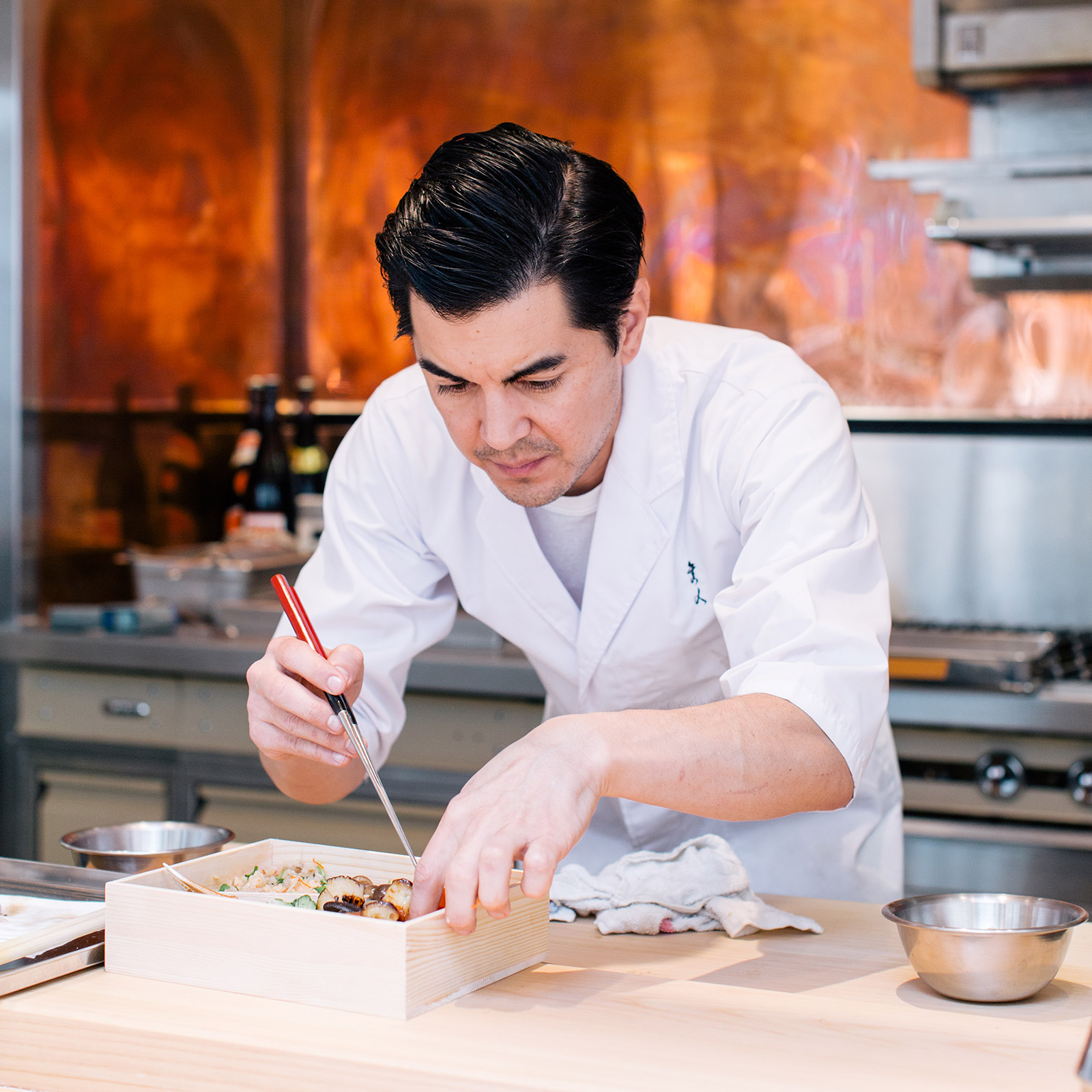 chef plating a box with japanese food in kitchen