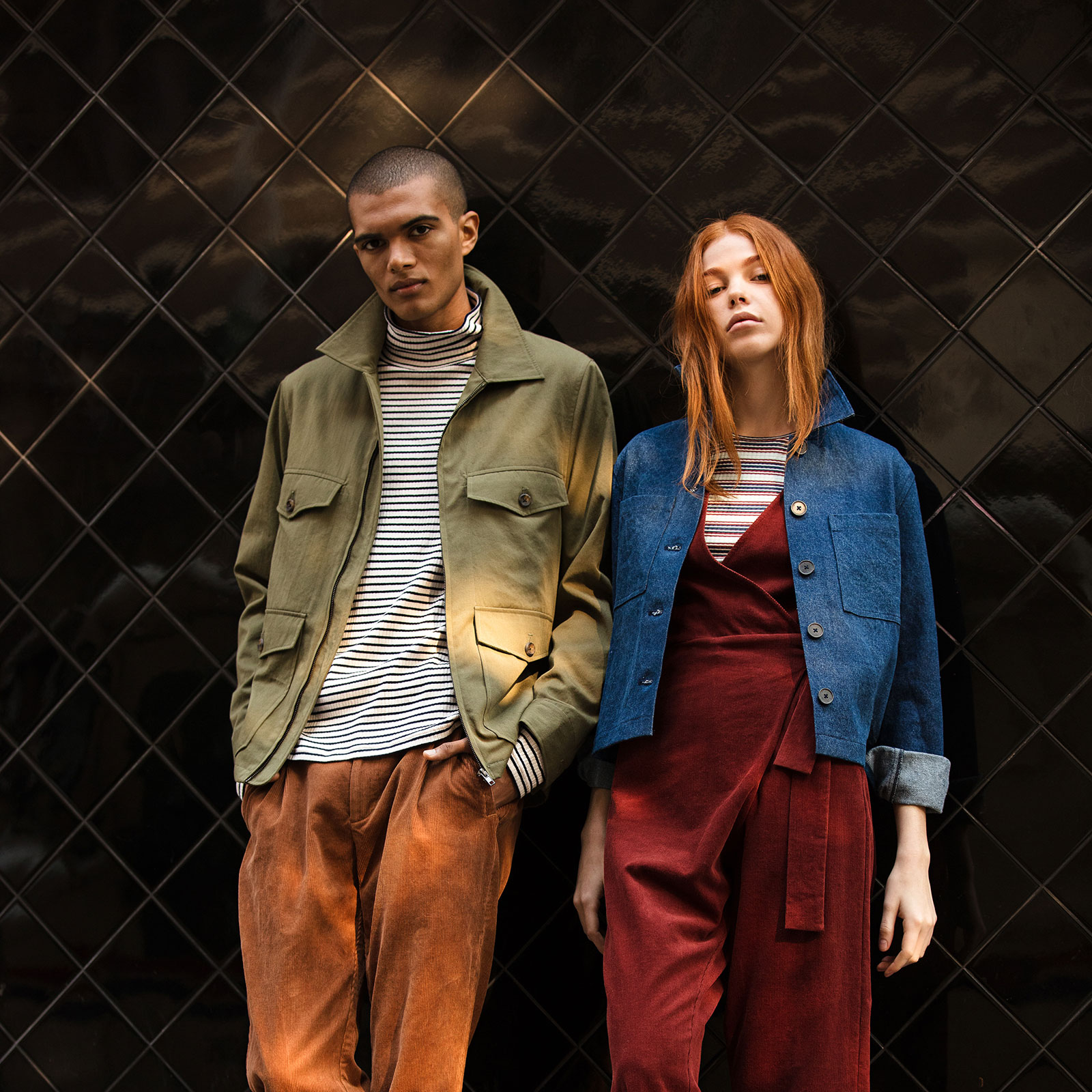 man wearing khaki jacket and orange pants leaning against a wall next to a woman wearing denim jacket and red jumpsuit