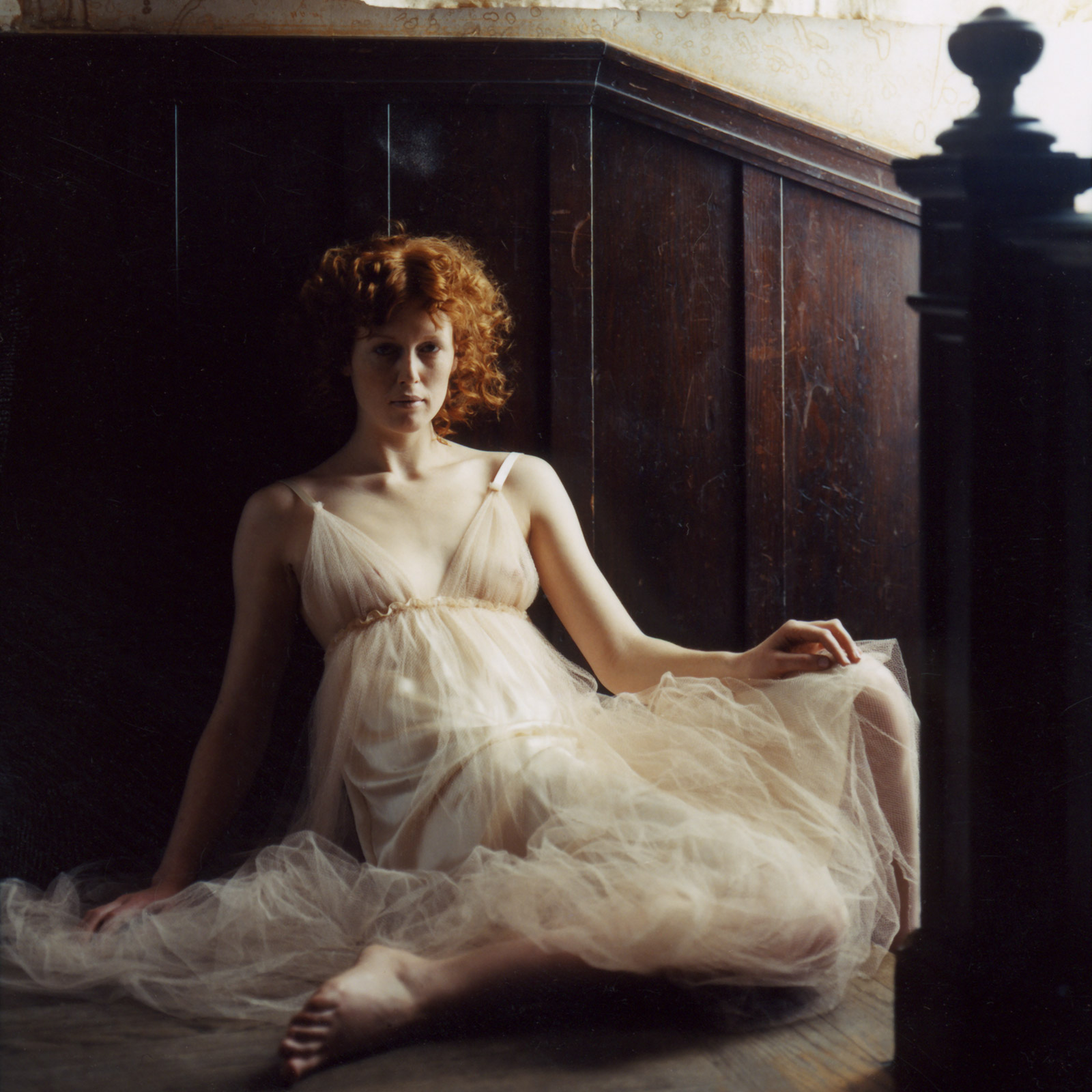 woman with red hair sitting at top of staircase wearing long white dress