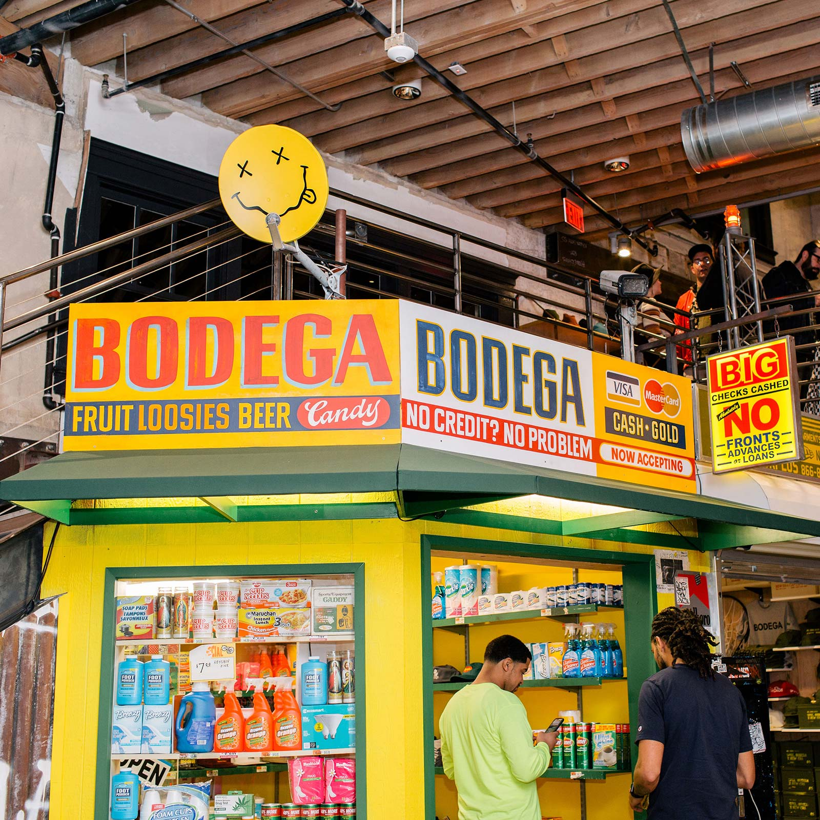 two people standing in front of a store with sign bodega