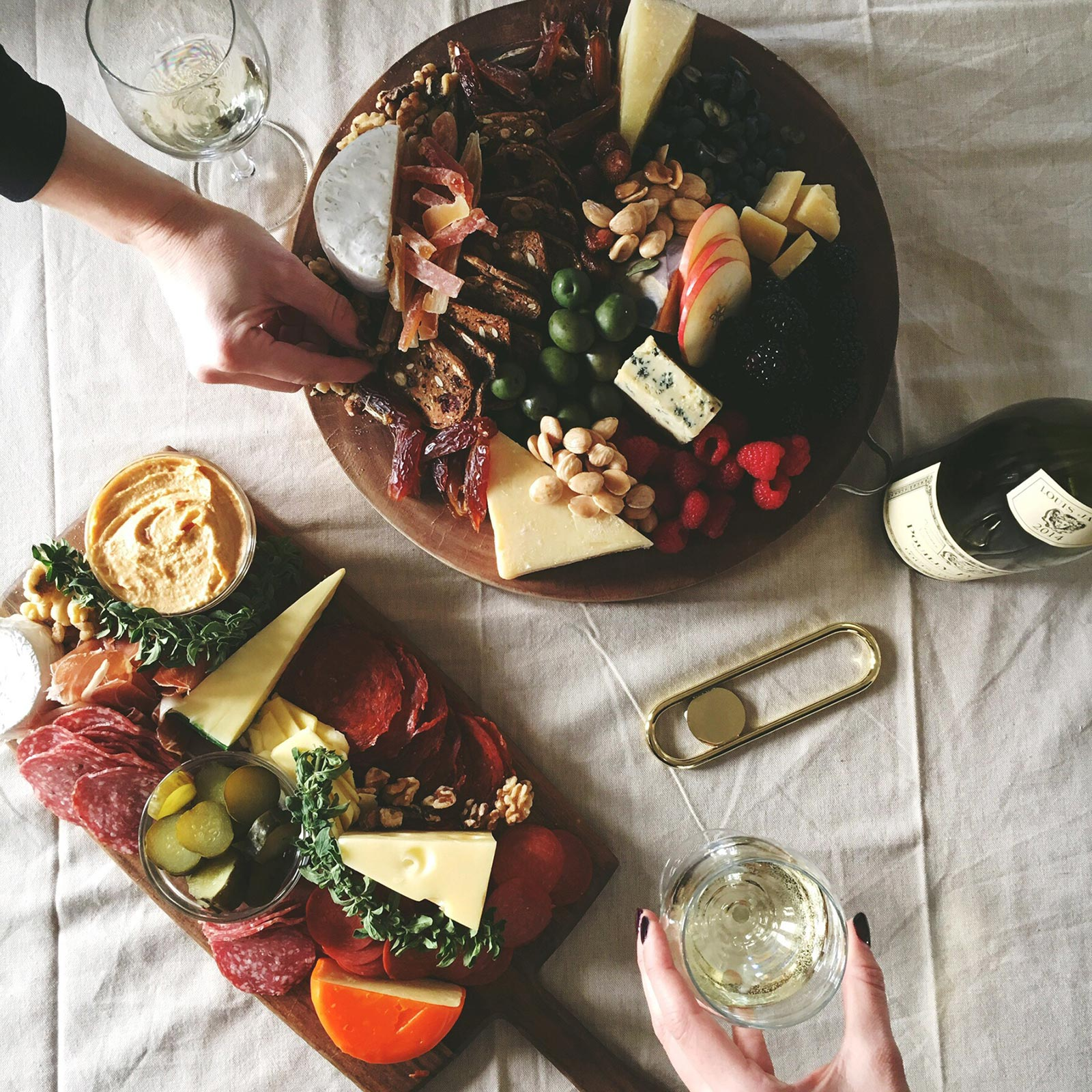 flat lay of charcuterie and cheese plate with wine glasses and bottles and a bottle opener