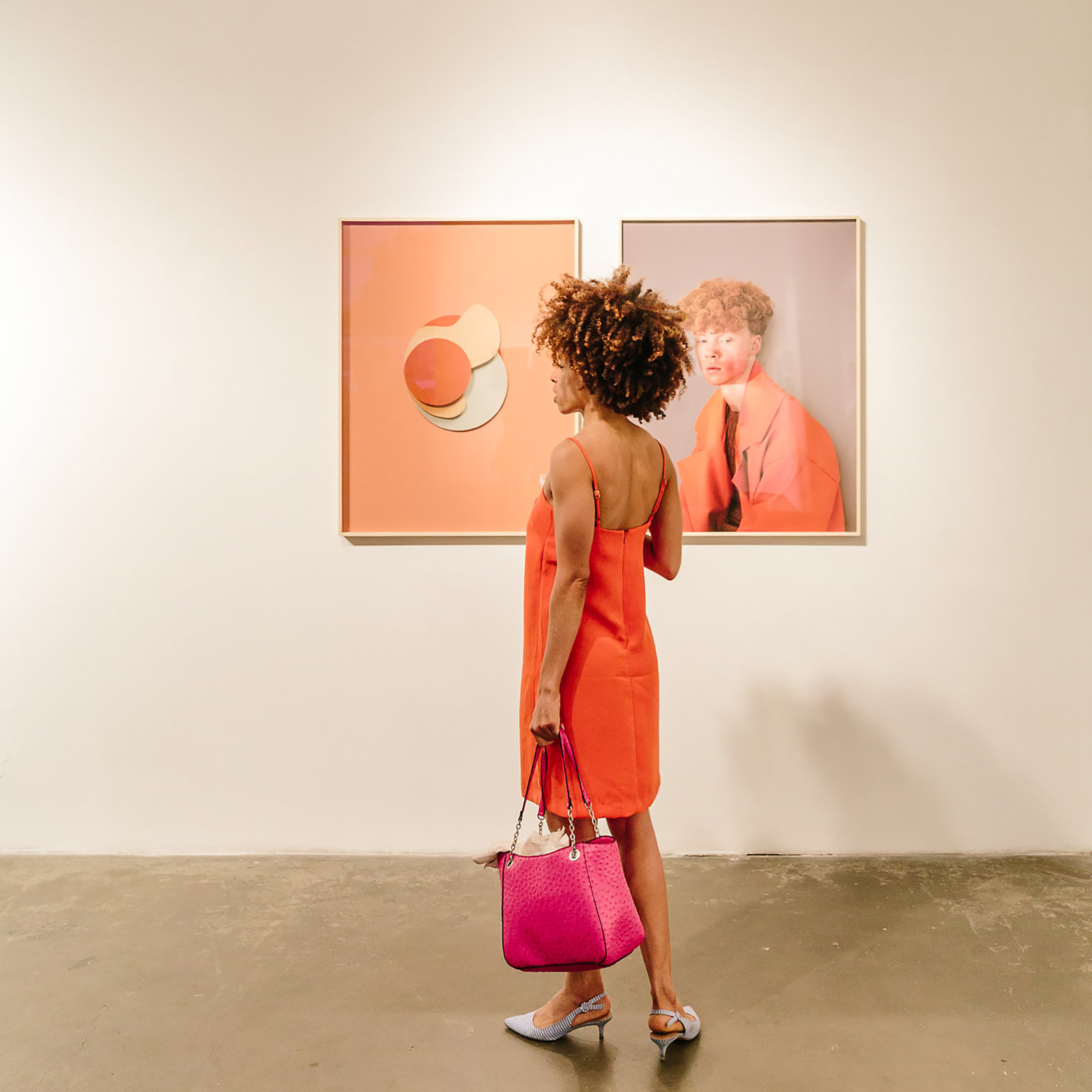 woman in orange dress holding pink bag standing in front of two paintings