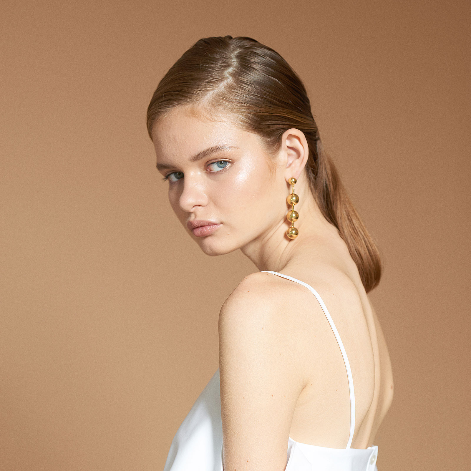 woman looking at camera sideways with gold earrings and white tank top