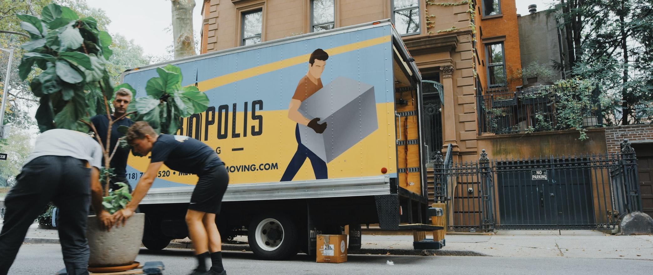 Une entreprise de déménagement dans la rue avec un camion.