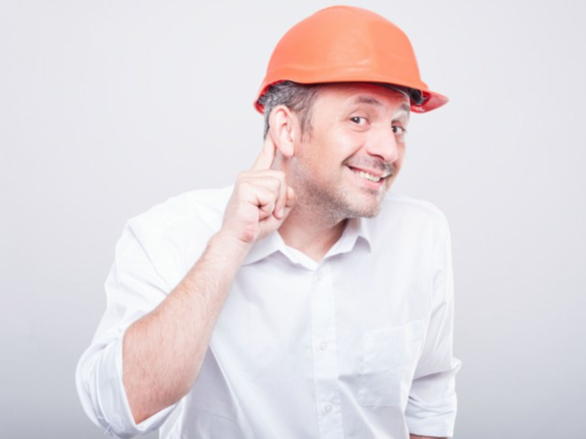 Man in hard hat trying to listen