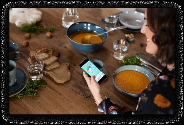 Frau isst Suppe und hat Handy in der Hand