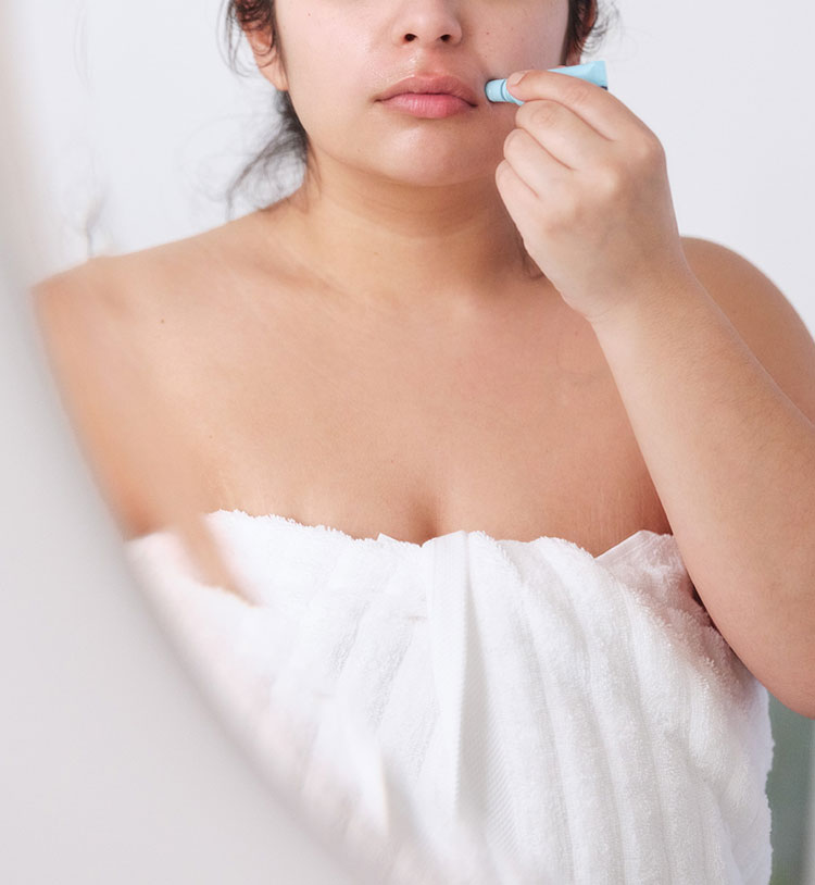 Woman applying calming serum.