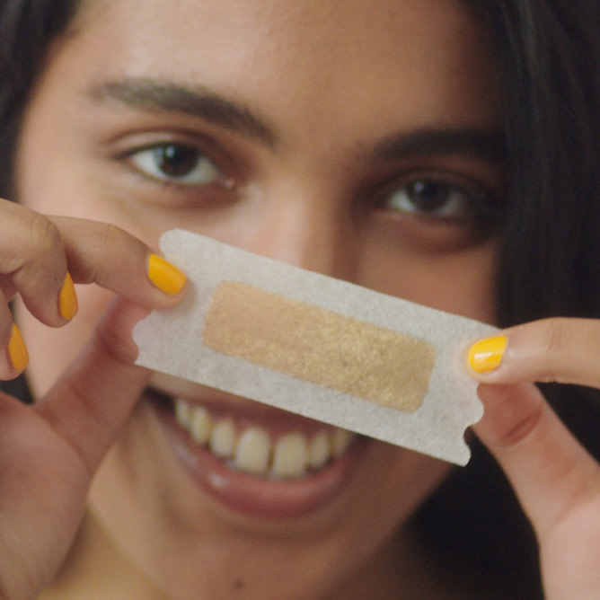 Woman holding face wax strip in front of face