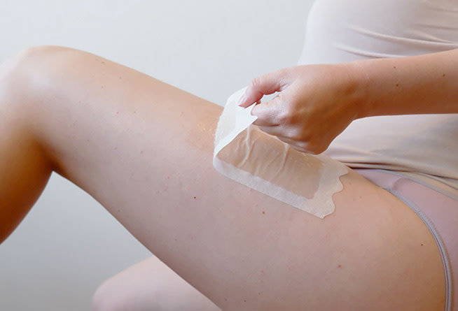 Woman pulling wax strip from upper thigh.