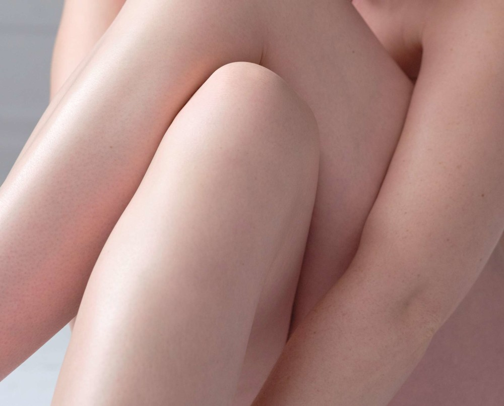 Woman's arms wrapped around her legs, highlighting her hydrated body skin