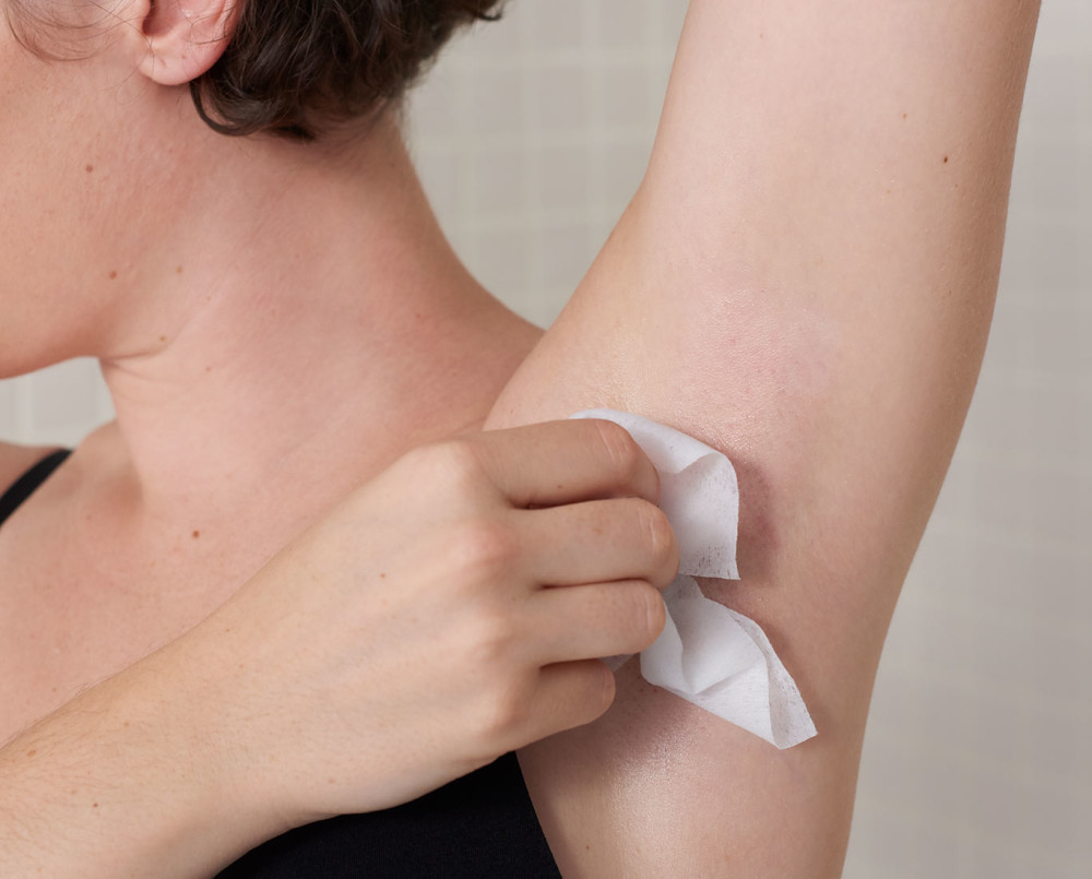 Woman removing wax from her underarm with plush, post-wax cloth