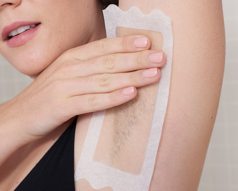 Woman pressing a soft gel body wax strip into her underarm hair