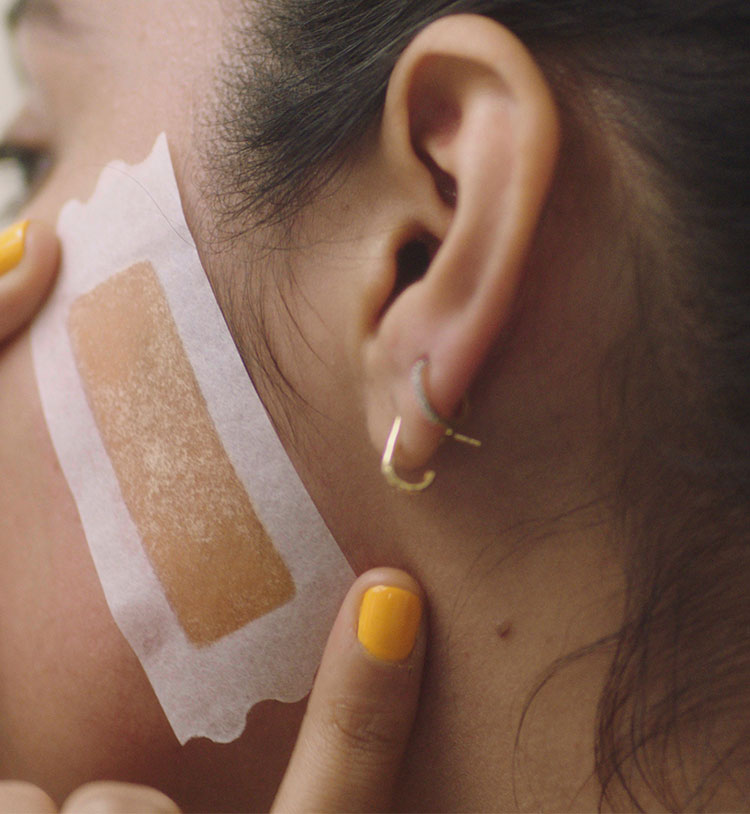 Woman applying wax strip to sideburn.