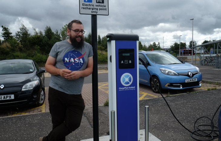 Man standing next to an electric charging station