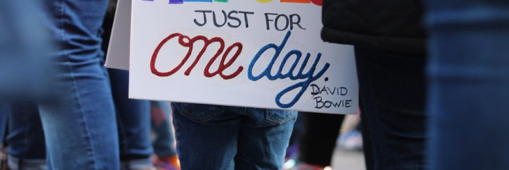 "You girl wearing placard. ""We can be heroes just for one day. David Bowie"""