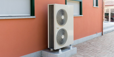 Heat pump against pink house