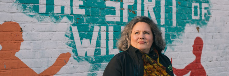 Debbie Mitchener standing in front of a wall with graffiti.